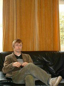 Neil Hannon (The Divine Comedy) sitzt auf dem Sofa